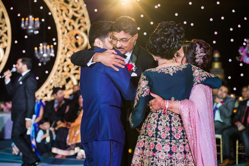 Indian Bride and Groom doing Hug with their Parents