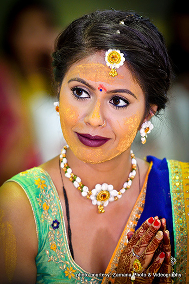 Indian Bride Applying Haldi on her Face during Pre Wedding Ceremony