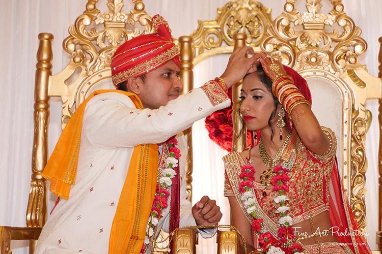Indian Groom applying Sindoor to the Bride