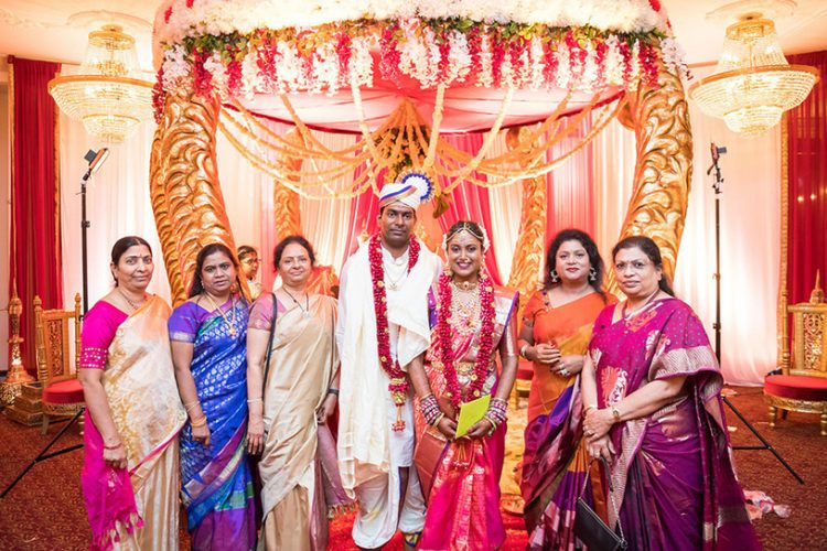 Indian Bride and Groom Possing with their Mother's Friend