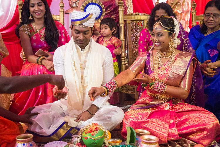 Indian Bride and Groom Putting Grains on Coconut