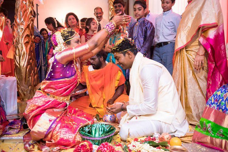 Indian Bride putting Grains on Indian Groom's Head