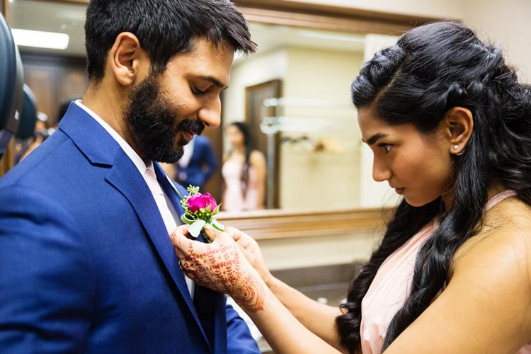 Indian Groom's Sister Ties Flower on Groom's Suit