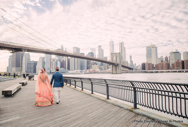 Indian Bride and Groom walking on bridge with holding hands