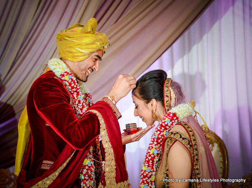 Indian Groom applying Sindoor to Bride