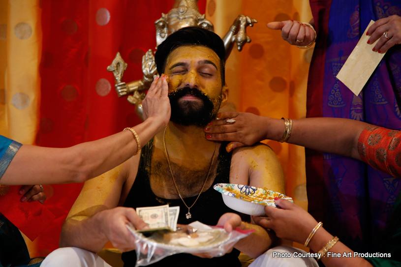 Family members Applying Haldi to indian Groom