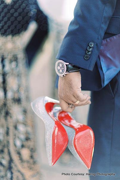 Indian Groom holding footwear of Indian bride